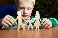 Schutz, Kind mit Papierfamilie Stockbild