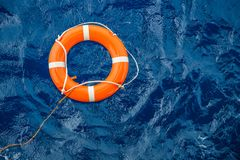 Schutzausrüstungs-, Lebenboje oder Rettungsboje, die auf Meer schwimmt, um Leute vom Ertrinken des Mannes zu retten lizenzfreie stockfotografie