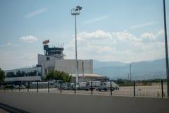 Schutzblech internationalen Flughafens Skopjes mit Kontrollturm, Landungsbrücke und Adria Airways Airplane auf Asphalt stockbild