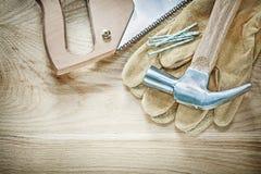 Schutzhandschuhe des Tischlerhammers scharfe Handsawnägel auf hölzernem Eber Lizenzfreie Stockfotos