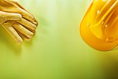 Schutzhandschuhe, die Sturzhelm auf gelbem Hintergrund errichten Stockfotografie