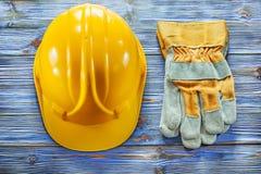 Schutzhandschuhe, die Sturzhelm auf hölzernem Brett der Weinlese errichten Lizenzfreie Stockbilder