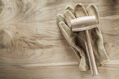Schutzhandschuheklumpenhammer auf hölzernem Brett Lizenzfreie Stockbilder