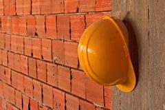Schutzhelm, der an der Betonmauer hängt Lizenzfreies Stockfoto