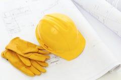 Schutzhelm- und Arbeitshandschuhe auf Heimwerkenpläne Lizenzfreie Stockfotografie