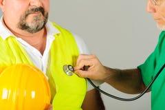 Schutzhelmarbeit an Arztprüfung Stockfotografie