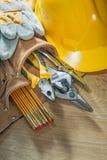 Schutzhelmschutzhandschuhe bearbeiten Gurtwerkzeugausstattung auf hölzernem Brett Stockfoto