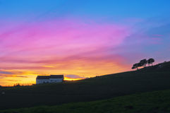 Schuur en bomensilhouet tegen zonsonderganghemel Royalty-vrije Stock Afbeeldingen