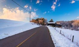 Schuur en sneeuw behandelde gebieden langs een landweg in landelijk York Stock Afbeelding