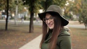 Schuw jong meisje in het de herfstpark Verschillende emoties, niet handigheid stock video
