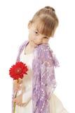 Schuw meisje dat in kleding rode bloem houdt Stock Foto's