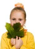 Schuw meisje met groen esdoornblad in zijn hand Stock Afbeeldingen