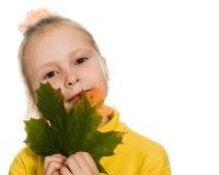 Schuw meisje met groen esdoornblad in zijn hand Royalty-vrije Stock Afbeelding
