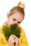 Schuw meisje met groen esdoornblad in zijn hand Royalty-vrije Stock Foto