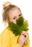Schuw meisje met groen esdoornblad in zijn hand Stock Foto