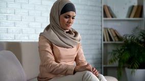Schuwe moslim vrouwelijke zitting op bank thuis, wachtenechtgenoot van het werk, huwelijk royalty-vrije stock afbeeldingen