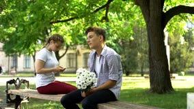 Schuwe tiener die met bloemen naast dame, surfen zitten netto op telefoon, aarzeling stock afbeeldingen