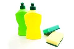 Schwämme und farbige Flaschen auf Weiß Stockfotografie