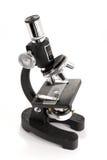 Schwärzen Sie das Mikroskop, das auf weißem Hintergrund getrennt wird Lizenzfreie Stockbilder