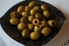 Schwärzen Sie kopierte Platte mit Oliven auf der weißen Tischdecke Stockfotos