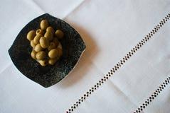 Schwärzen Sie kopierte Platte mit Oliven auf der weißen Tischdecke Lizenzfreie Stockfotos