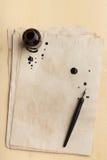 Schwärzen Sie Stift auf dem alten Papier mit Stellen mit Tinte Stockfoto