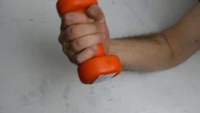 Schwach, ohne männlichen Arm der Muskeln tut eine Übung mit einem orange Dummkopf stock video