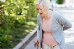 Schwacher Pensionär, der unter Rückenschmerzen auf der Straße leidet Lizenzfreie Stockfotografie