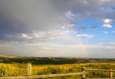 Schwacher Regenbogen in den regnerischen Himmeln über dem Alberta-Grasland und in den Vorbergen an der Ranch Stockbilder