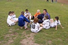 Futbolowy trener z drużyną dyskutuje grę Zdjęcia Royalty Free