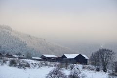 Schwalefeld, Germany - February 5th, 2018 - Dark wooden farm buildings on a snowy hillside with distant misty mountains in the bac. Schwalefeld, Germany Stock Photos