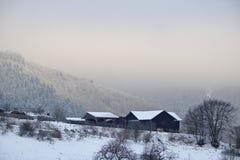 Schwalefeld Tyskland - Februari 5th, 2018 - mörka trälantgårdbyggnader på en snöig backe med avlägsna dimmiga berg i bacen Arkivfoton
