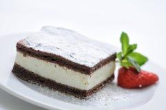 Schwammkakaokuchen mit Klumpen mit Pulverzucker, tadellosem Blatt und Erdbeere auf weißer Platte, Isolat auf weißem Hintergrund Stockbild