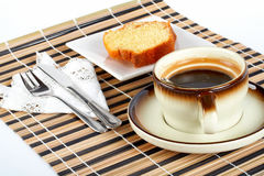 Schwammkuchen mit dem Löffel innerhalb des Tasse Kaffees, des Messers und der Gabel stockfotografie