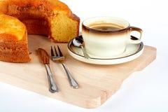 Schwammkuchen mit dem Tasse Kaffee, dem Löffel, dem Messer und der Gabel auf hölzerner Platte stockbild