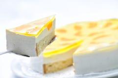 Schwammkuchen mit Sahne, Frucht und gelbe Gelatine auf dem Metalllöffel, scharf auf weißer Platte, Konditorei, Fotografie für Sho Stockfotos
