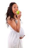 Schwangere Afroamerikanerfrau, die einen Apfel isst Stockfotos