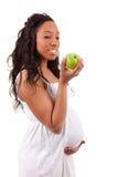 Schwangere Afroamerikanerfrau, die einen Apfel isst lizenzfreies stockfoto