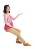 Schwangere Asiatinhand, die leeren Raum zeigt lizenzfreie stockfotos