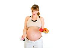 Schwangere bildenwahl zwischen Pillen und Früchten Stockfotos