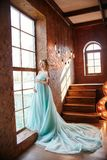 Schwangere Brautblondine bereitet vor sich, eine Mutter und eine Frau zu werden Langes Türkiskleid auf einem Mädchenkörper Gelock Stockfotografie