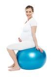 Schwangere Dame, die auf Übungskugel sitzt Stockbild