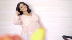 Schwangere Dame, die ihren Bauch, lächelnd berührt Schauen Sie durch Tulpen 4K stock video