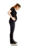 Schwangere Dame, die sich wiegt Stockbild