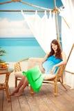Schwangere Frau auf dem Strand im Bungalow lizenzfreie stockbilder