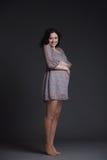 Schwangere Frau auf dunklem Hintergrund Lizenzfreie Stockfotografie