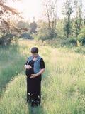 Schwangere Frau auf einem Gebiet für Mutterschaftsfotos Lizenzfreie Stockfotografie