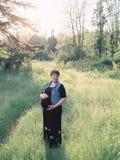Schwangere Frau auf einem Gebiet für Mutterschaftsfotos Lizenzfreies Stockbild