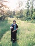 Schwangere Frau auf einem Gebiet für Mutterschaftsfotos Lizenzfreie Stockbilder