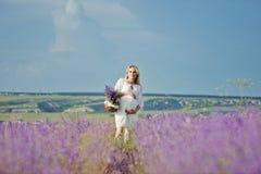 Schwangere Frau auf einem Lavendelgebiet Lizenzfreie Stockfotografie